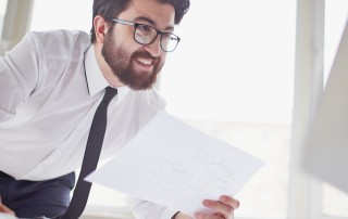 Happy businessman with paper in hand looking at computer monitor in office
